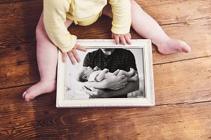 Unrecognizable baby holding picture frame. Fathers day.