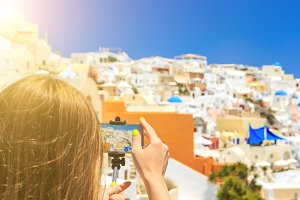 back view of standing young beautiful woman using mobile phone photographing types of Santorini.