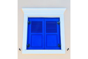 Traditional rectangular wooden closed window on a bright pink wall , architecture details Santorini, Greece