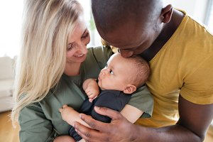 Young interracial family with little baby son at home.