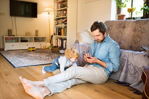 Young father with smartphone and his little son at home