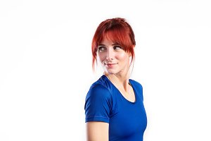 Attractive young fitness woman in blue t-shirt. Studio shot.