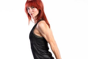 Attractive young fitness woman in black tank top. Studio shot.