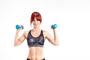 Young fitness woman working out with barbells. Studio shot.
