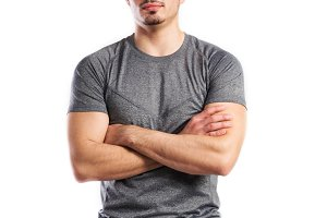 Young handsome fitness man in gray t-shirt, studio shot.