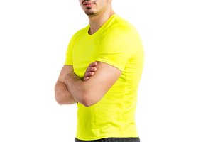 Young handsome fitness man in yellow t-shirt, studio shot.