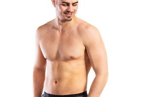 Shirtless fitness man, hands in pockets . Studio shot.