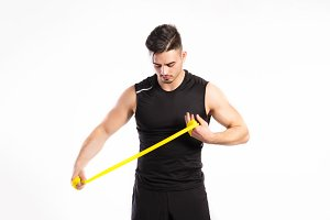 Handsome fitness man working out with rubber band, studio shot.