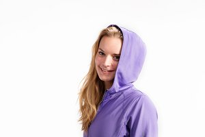 Young fitness woman in purple sweatshirt. Studio shot.