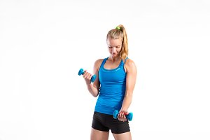 Attractive young fitness woman holding dumbells. Studio shot.