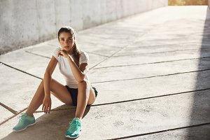Confident and fit female runner preparing to start her everyday marathon looking at camera smiling. Urban sport concept.