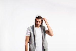 Handsome fitness man in vest with hood, studio shot.