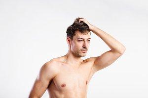 Shirtless fitness man holding his hair. Studio shot.