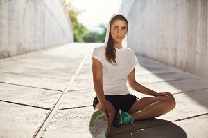 Runner lady stretching before her everyday evening park jogging. Urban sport concept.
