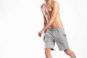 Shirtless fitness man in gray shorts. Studio shot.