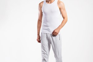 Handsome fitness man in white tank top shirt, studio shot.