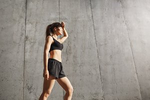 Sporty woman looking into sun in concrete urban environment, getting ready for her excercise.