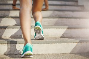 Close up of young woman sporty legs preparing to run upstairs on her everyday urban workout. Healthy lifestyle concept.