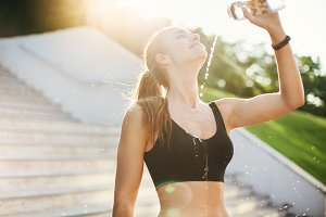Young female runner pouring water over herself after a long and hard morning workout. Urban sport and lifestyle concept.