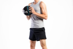 Handsome fitness man holding medicine ball, studio shot.