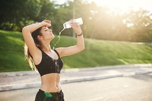 Young female fitness idol pouring water over her perfect body after a long and hard workout. Urban sport concept.