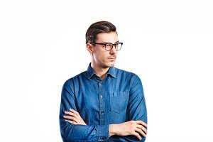 Handsome young man in denim shirt. Studio shot, isolated.