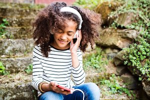 Beautiful african american girl with smart phone and earphones.