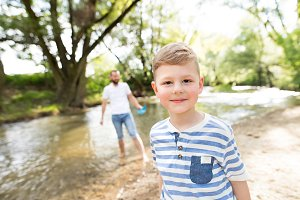 Little boy with his father at the river, sunny spring day.