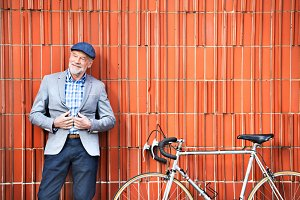 Senior man with bicycle standing against brick wall.