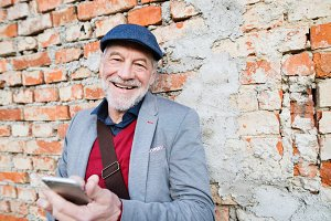 Senior man with smartphone against brick wall, texting.