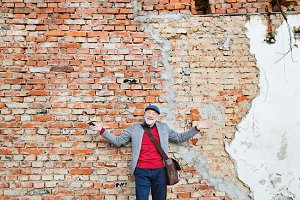 Senior man with smartphone against brick wall.