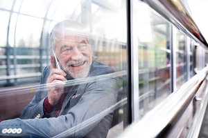 Senior man with smartphone in glass passage making phone call.