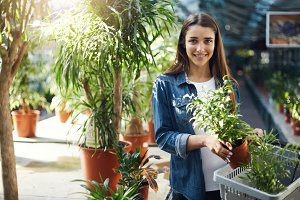 Young girl shopping for plants in a greenhouse looking at camera smiling.