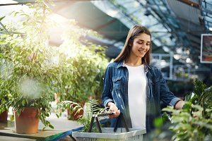 Beautiful girl shopping for green plants in a store. Planning to surprise her mother with a gift.