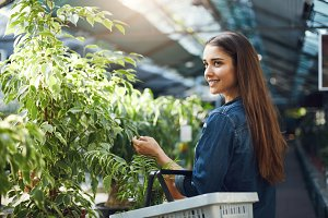 Young woman shopping for flowers and plants in a home garden store.