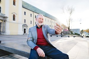 Senior man in town with smart phone, taking selfie.