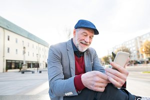 Senior man in town with smart phone, texting