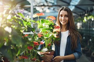 Young lady holding a flower in a greenery store shopping for plants for her backyard looking at camera smiling.