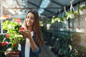 Young wife looking after plants in a greenhouse holding a pot with flowers.