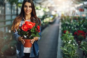 Young female entrepreneur holding a flower in her new greenery shop. Business concept.