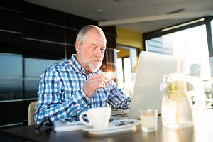 Senior businessman working on laptop in cafe
