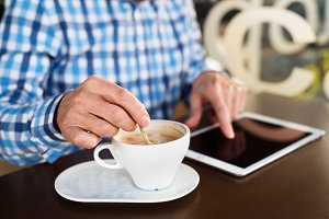 Unrecognizable senior businessman working on tablet in cafe