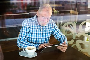 Senior businessman working on tablet in cafe