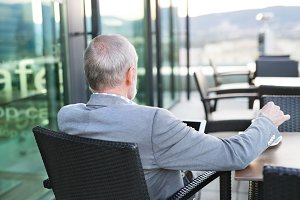 Senior businessman with a tablet in rooftop cafe