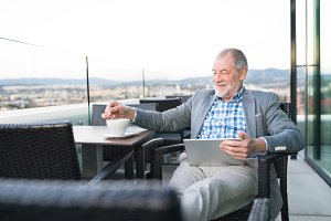 Senior businessman working on tablet in rooftop cafe