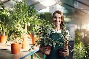 Young happy female gardener holding plants in pots in owner run greenery store