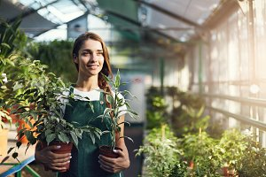 Female greenhouse store employee holding plants ready for sale