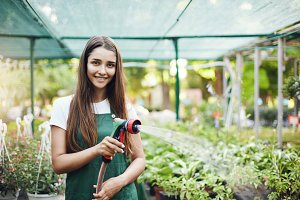 Happy young female gardener watering plants in owner operated greenhouse store.