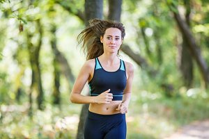 Young smiling woman running in park in the morning