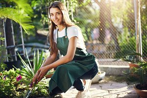 Young gardener taking care of plants in the backyard or an outdoor plant store